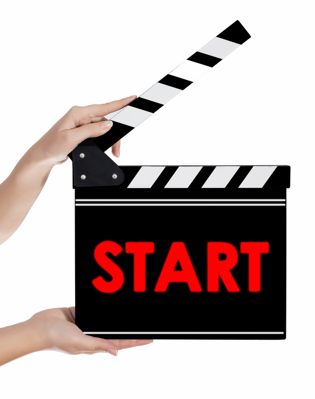 Hands holding a clapper board with START text